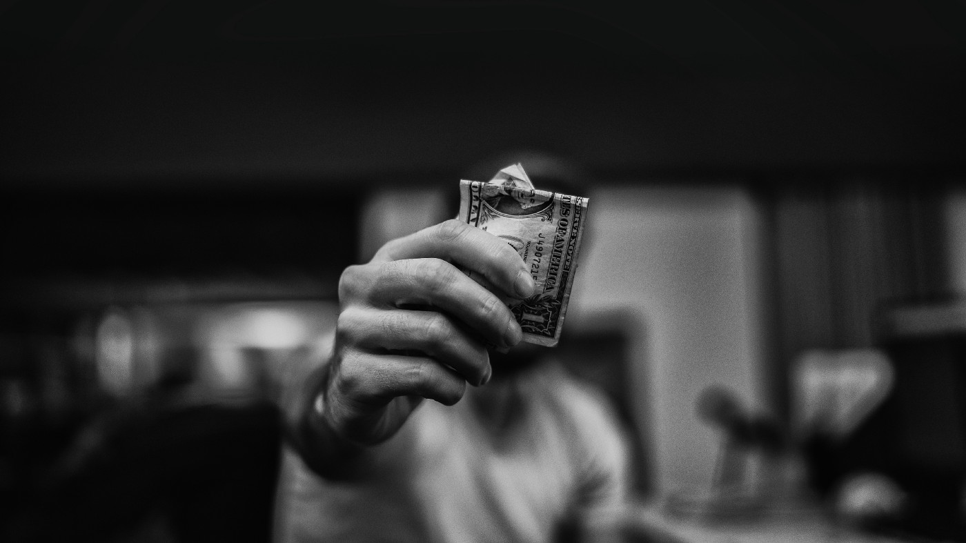 Person holding a 1-dollar bill.