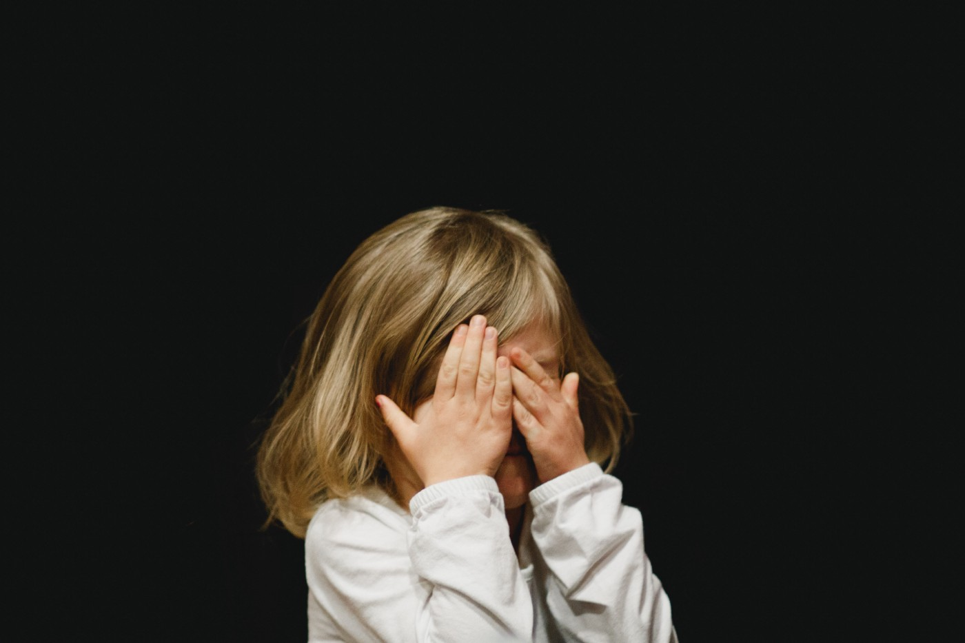 Young girl covers her eyes.