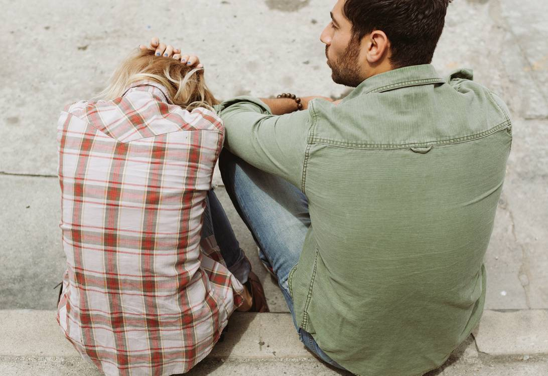 Two people sit on the sidewalk together. One has their head between their knees and their hands on their head. #relationship
