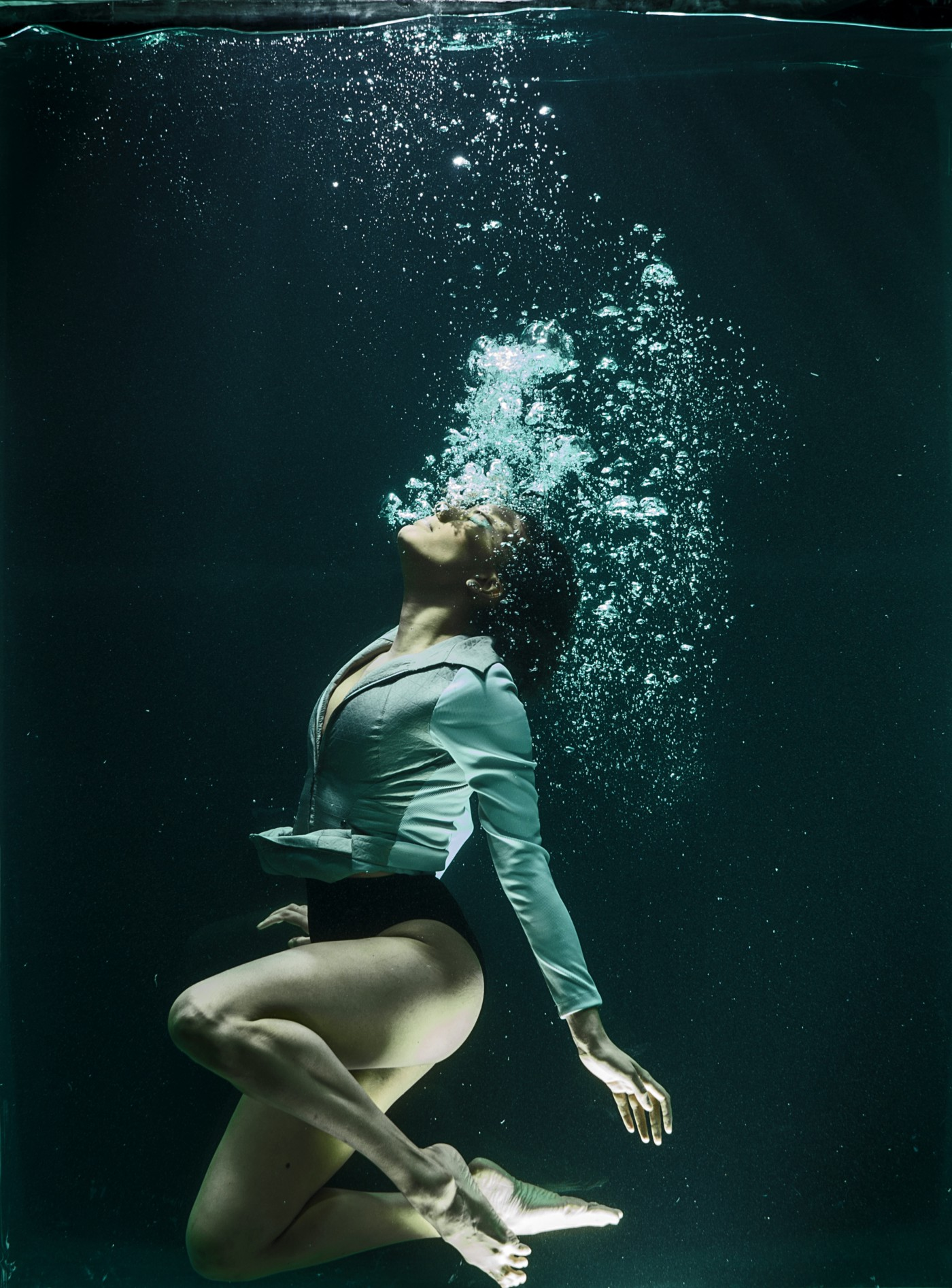 Woman under water, bubbles coming from her mouth. Dark, vertical photo.