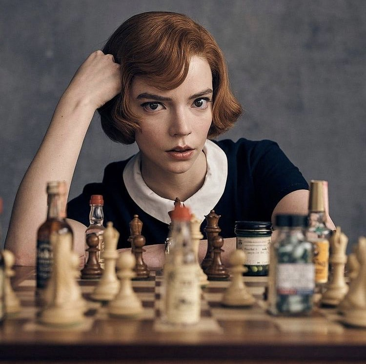 Beth Harmon sits at a chessboard, but some of the chess pieces are replaced by bottles of alcohol and pills.