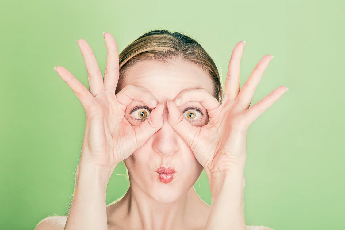 A woman holding her fingers round her eyes to imitate glasses on her face