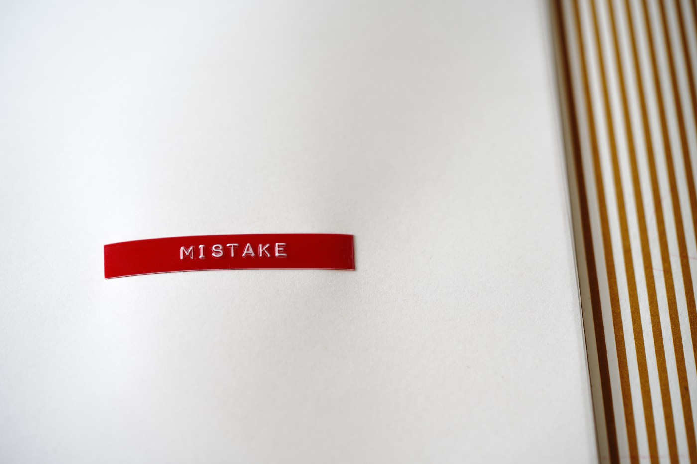 Red sticker with the word mistake on it in white font