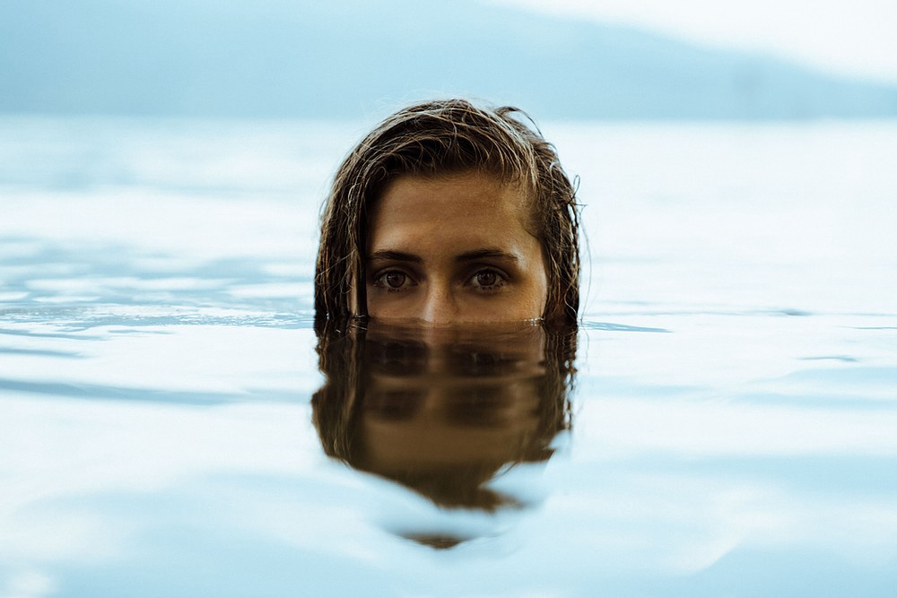 Woman almost entirely underwater, with her face from the nose up above the surface.
