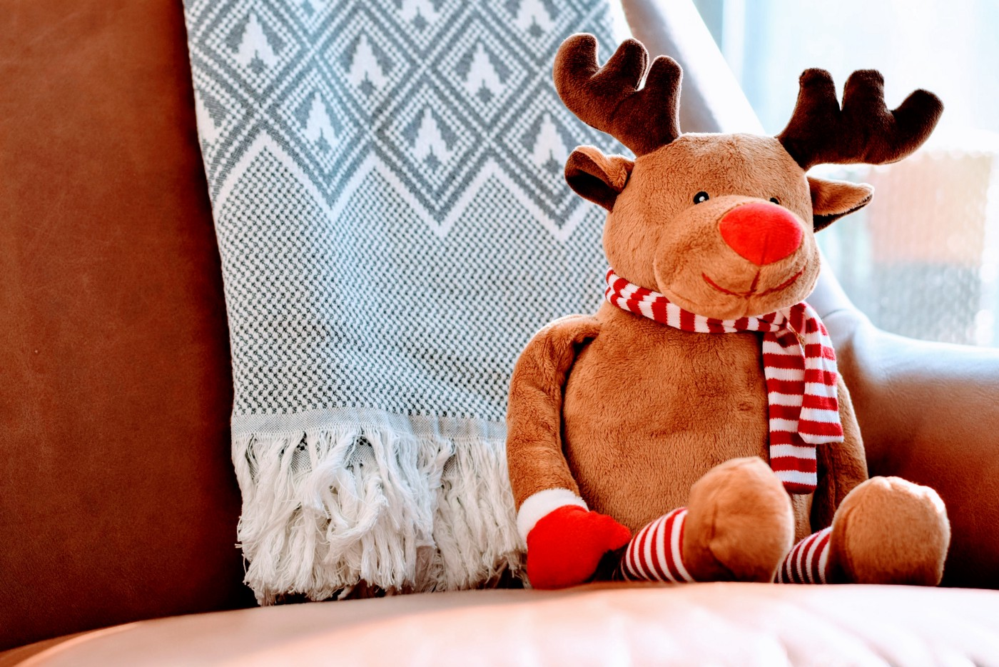 A stuffed Rudolph the Red Nosed Reindeer smiles and sits on a couch. He wears a striped candy cane scarf and matching gloves