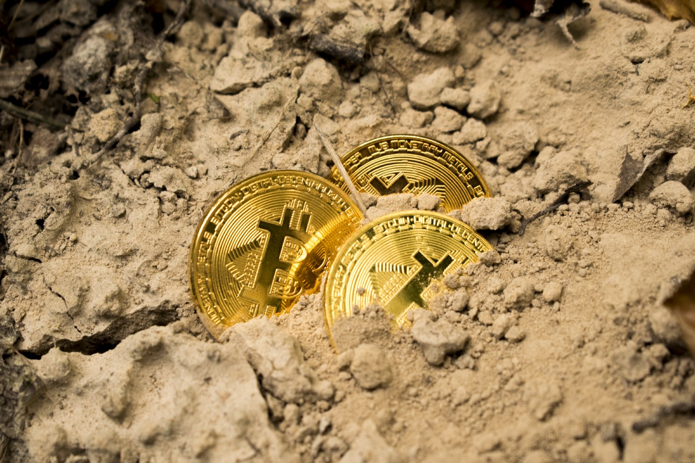 """Bitcoin """"coins"""" uncovered from dirt. A metaphor for """"mining"""" bitcoin."""