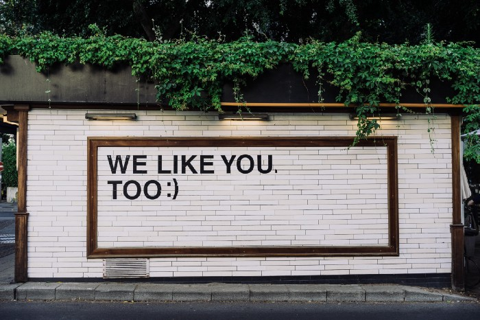 Billboard of a text message in black and white saying We Like You Too:-)