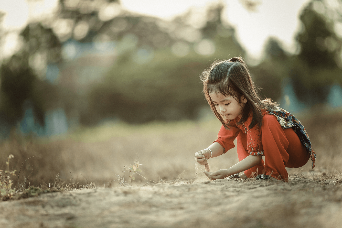 Girl in red playing with sand.