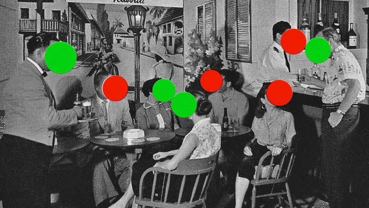 Vintage black-and-white photo of a party of 5 diners at 2 small round tables in front of a mural of a Parisian street inside a restaurant. A waiter is dropping off the beverage order, and 2 people converse at the bar that the tables are next to. All of the people have a solid green or a red circle imposed over their faces to represent vaccinated and unvaccinated people.