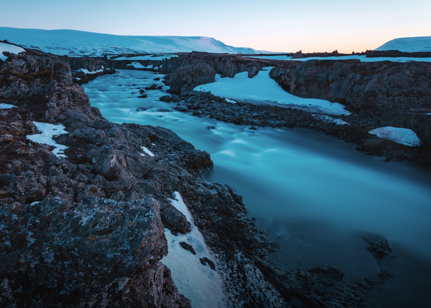 A steaming geothermal river in Iceland flowing through black volcanic rock