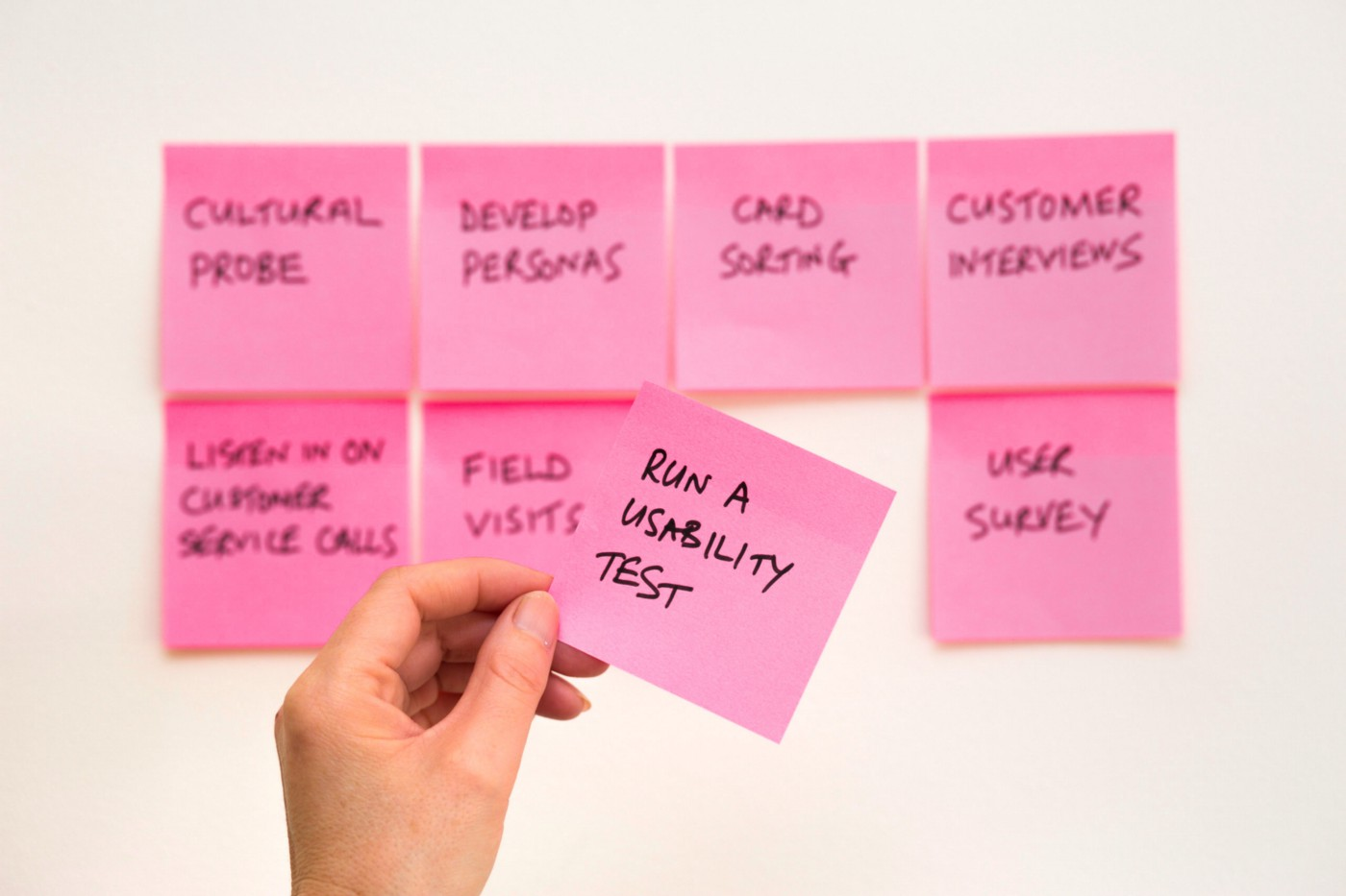 """Seven pink post-its stuck to the wall out of focus. A hand holds one post-it in focus that reads """"run a usability test."""""""