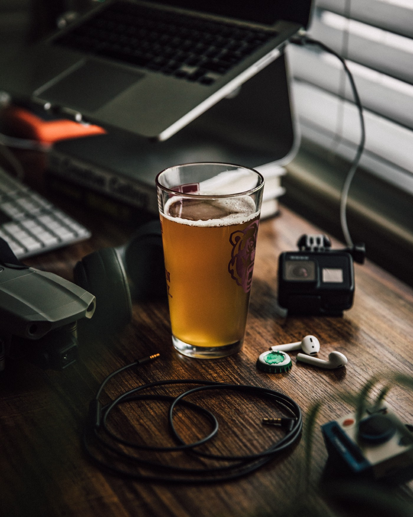 A glass of beer next to a keyboard and office equipment.
