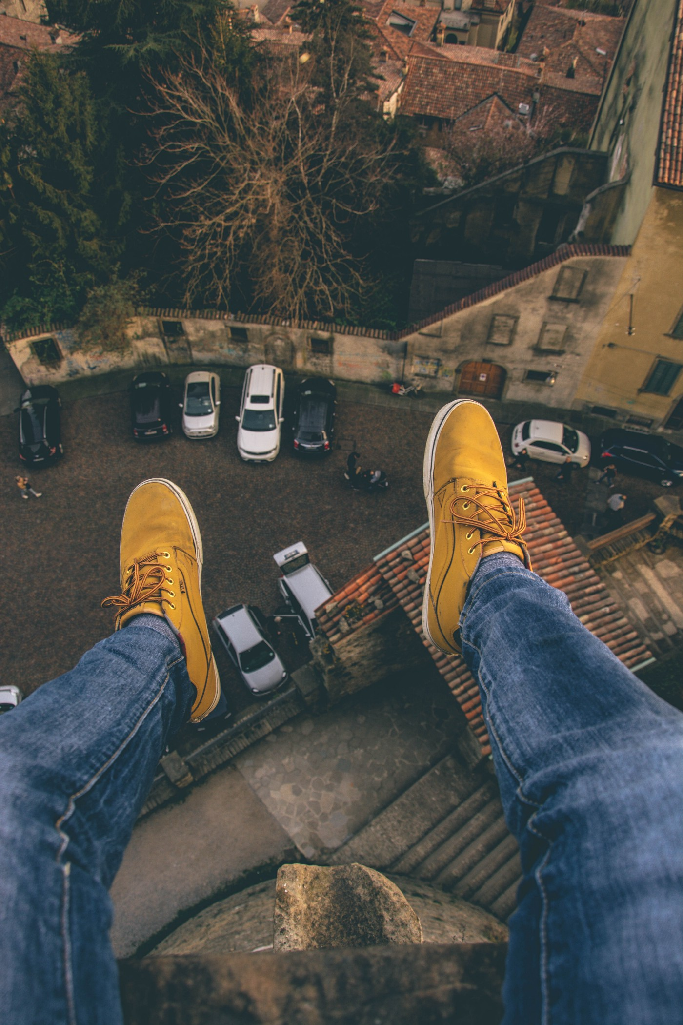 top-down view of the feet and legs of a person sitting on a rooftop overlooking a parking lot