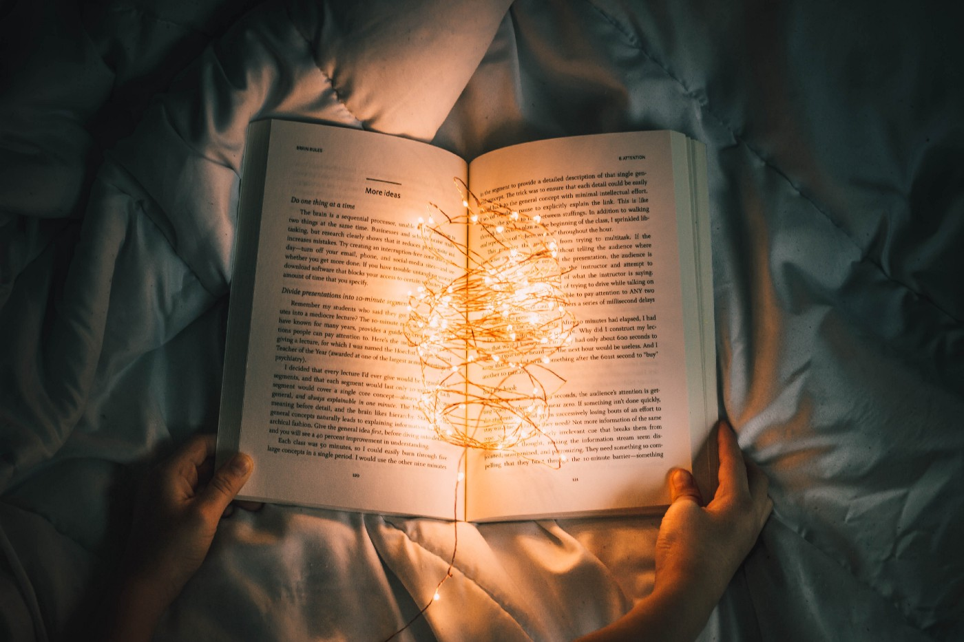 An open book on a blanket in a bed with lights inside the book, illuminating the pages