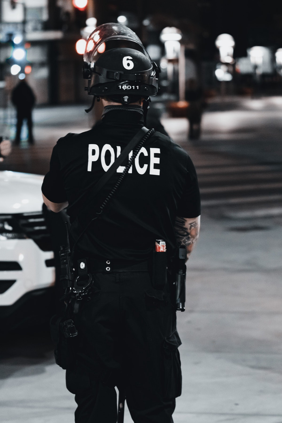 policeman facing away from the camera on a city street in the evening
