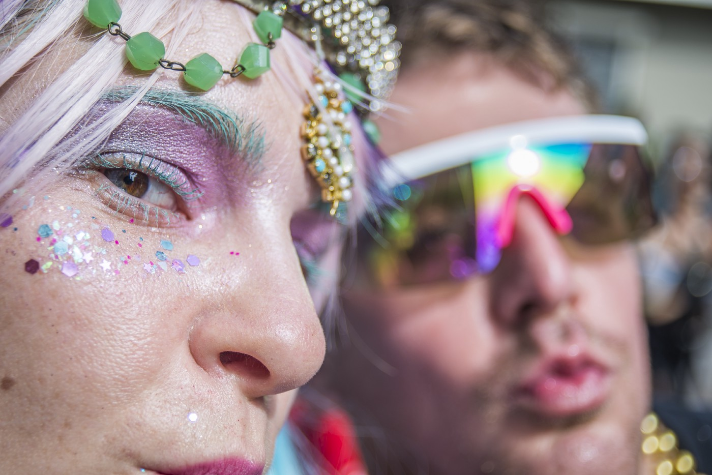 Close up of two people with colorful accessories.