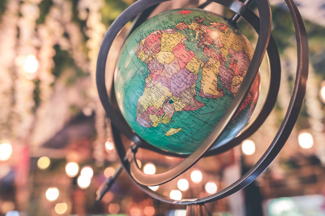 A globe tilted on its axis with colorful lights behind it.