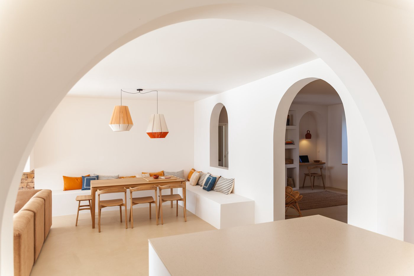 Arched doorways and windows have been introduced into the home to separate areas. Recessed wall niches hold a selection of art, ceramic pots, straw fans, and books. (Photo: Thibaut Dini, Life's A Beach)