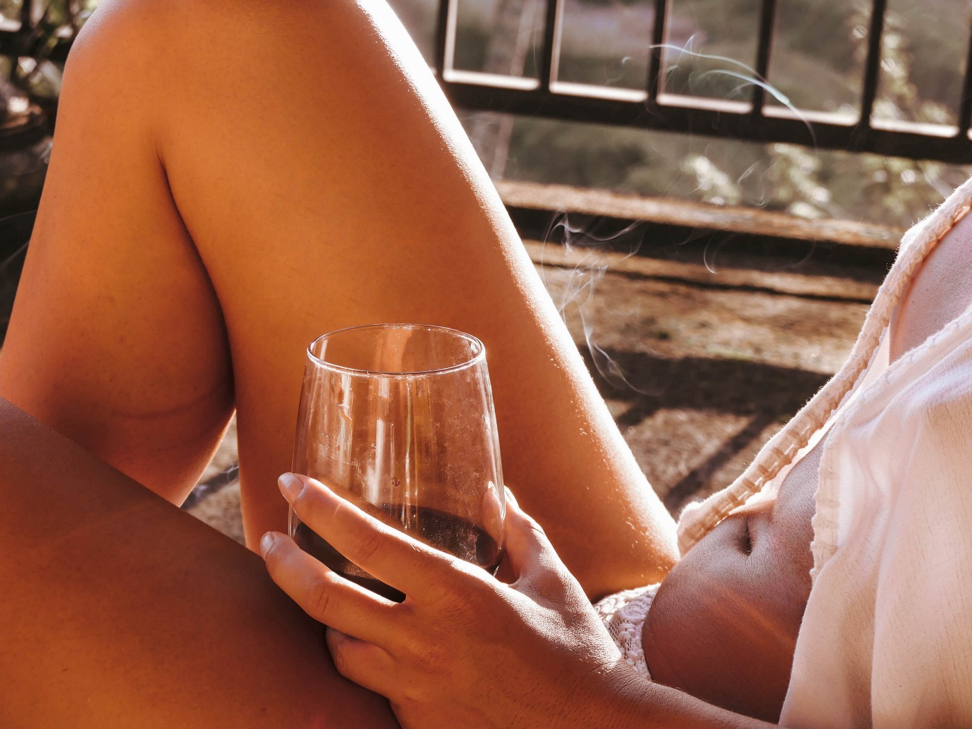 Partial view of a scantily clad woman holding a stemless glass of wine