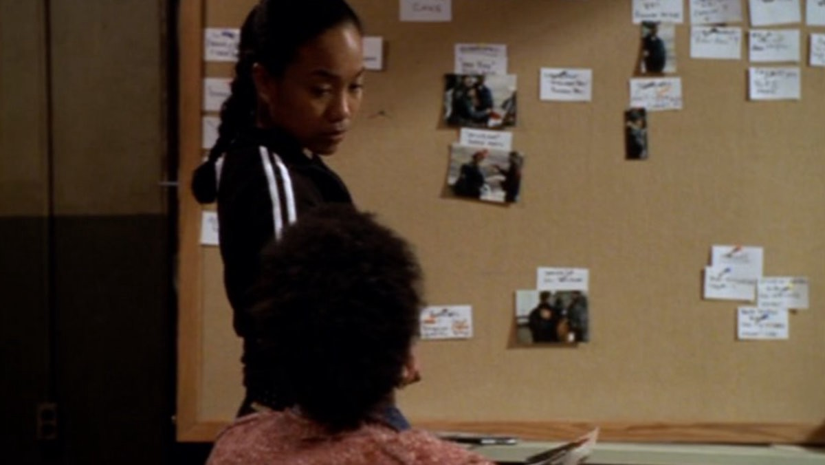 Kima and Bubbs of HBO's»The Wire«discuss a case in front of a pinboard