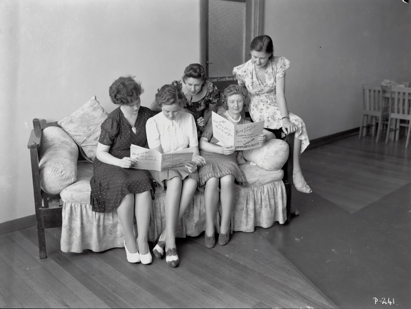 A black and white photo of women in dresses and skirts gathered on a couch reading pamphlets