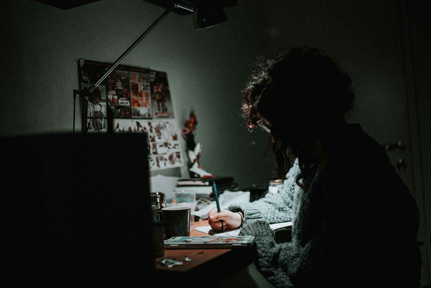 Girl writing by her desk under the light of a lamp