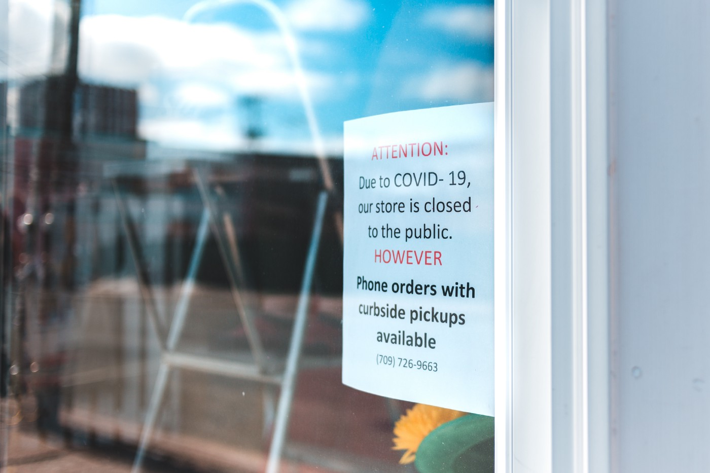 [Photo] Window with a sign announcing that due to COVID-10, they are closed to the public and offering curbside pickup.