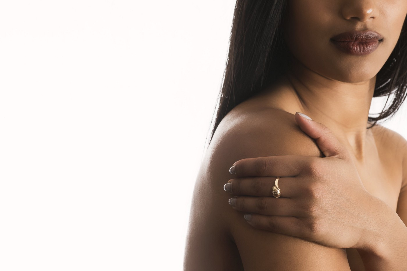 Woman showing nose to mid upper arm while shirtless holding upper right arm with left hand as if trying to hide upper arms bumps