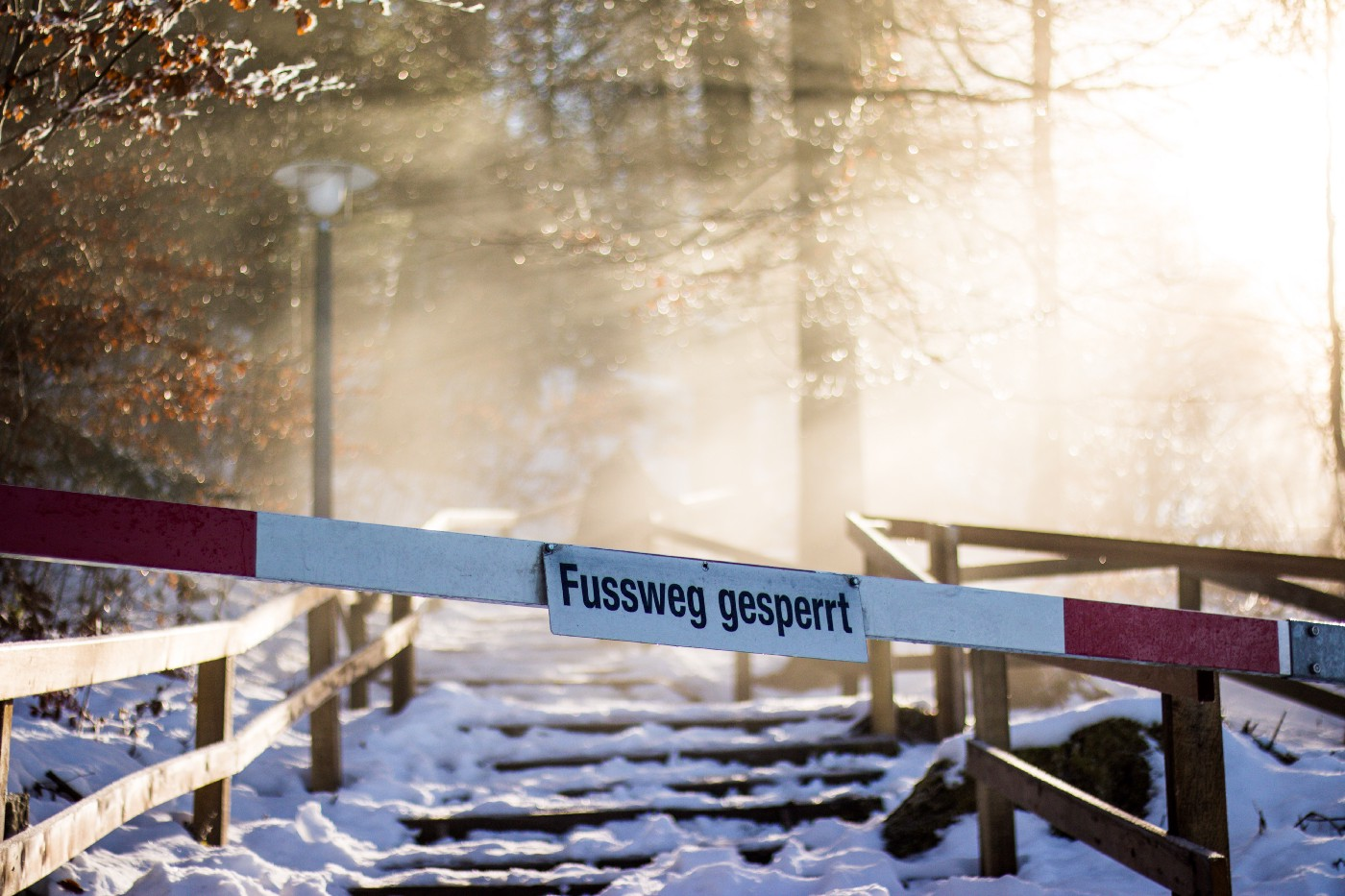 """A blockade standing in front of a forest background, with the words """"Fussweg gesperrt"""" written on it."""