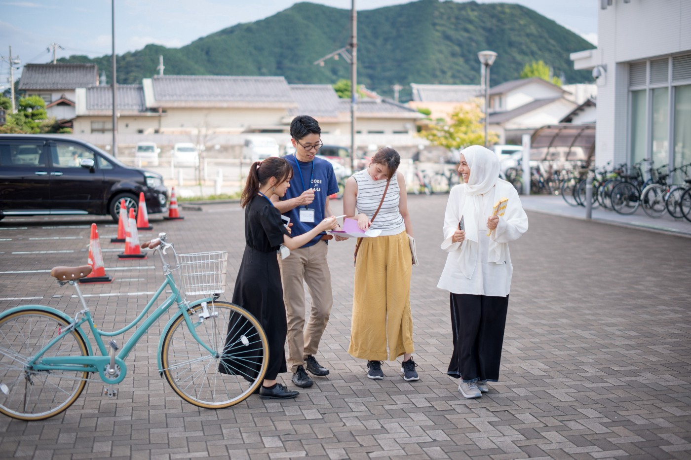 Photo of four people looking at a sheet of instructions. They are outside, on the plaza of a school, with mountains behind.