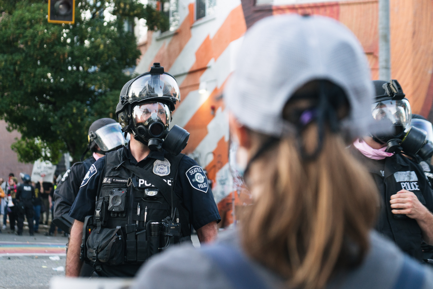 Seattle Police officer wearing a gas mask stands as a protester wearing a ball cap looks on.