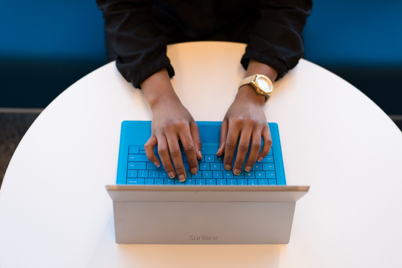 A woman's hands are poised over a laptop's keyboard on a table.