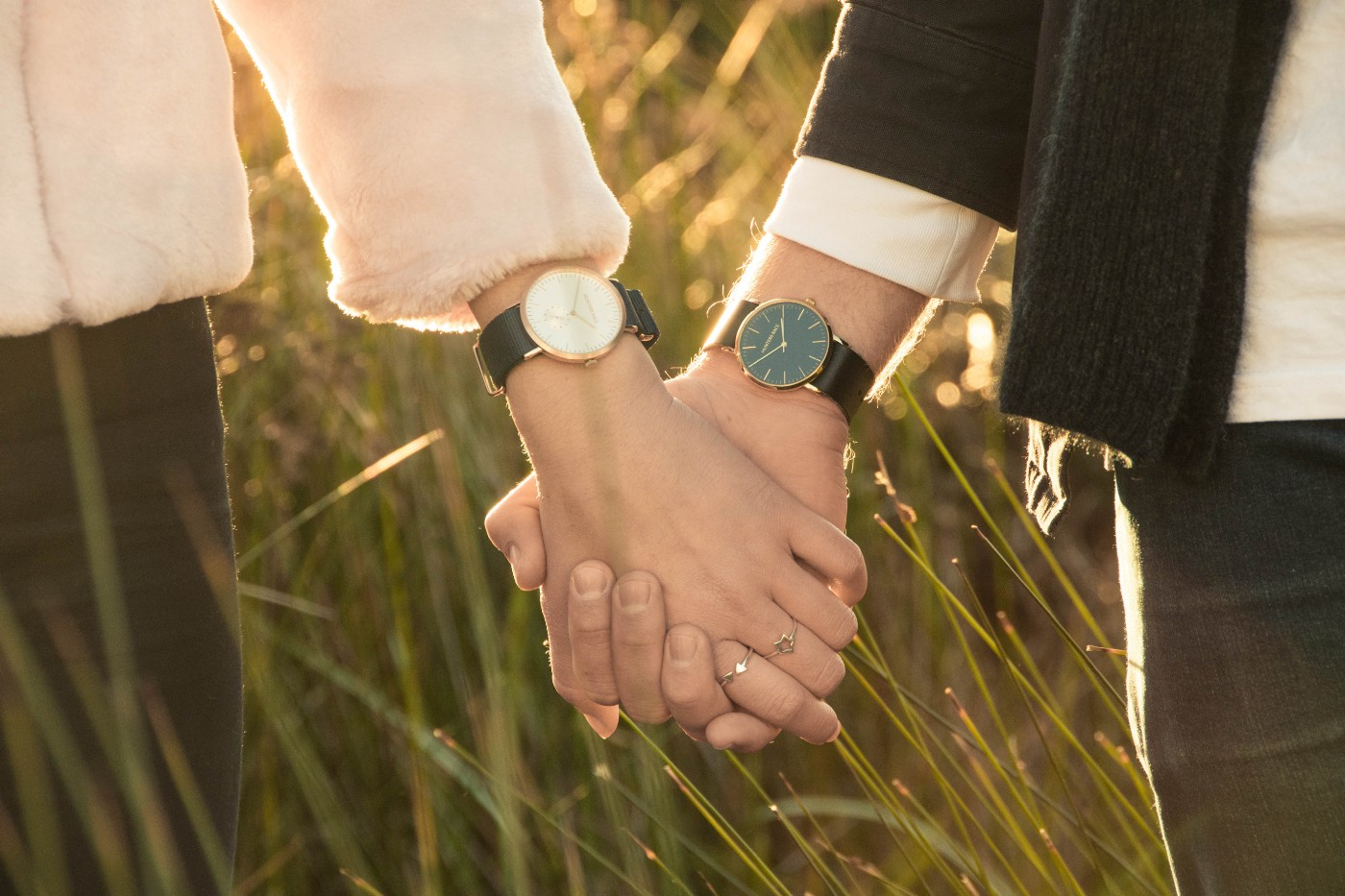 Two people holding hands in a field of grass, both wearing watches on their wrists.