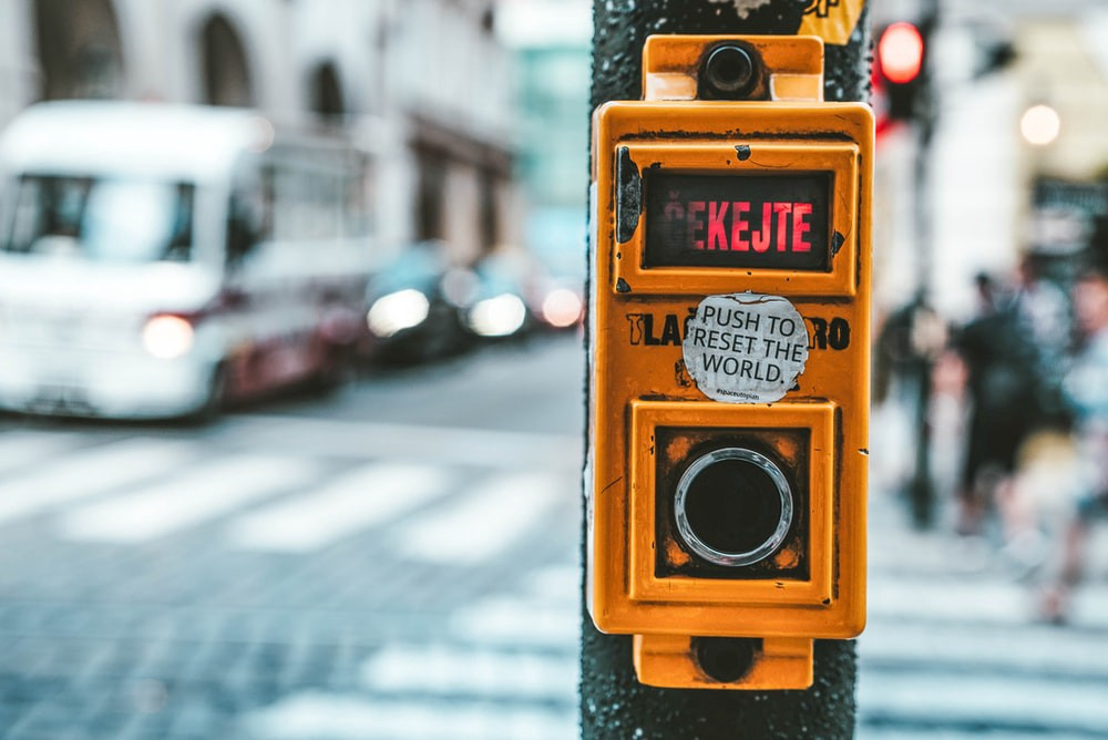 Traffic light with a sticker saying 'Push to Reset the World'