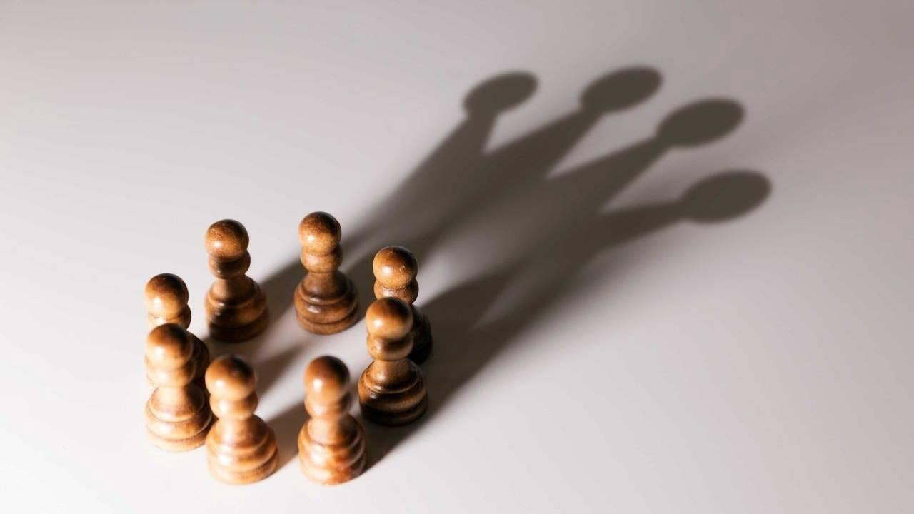 Circle of chess pawns whose shadow looks like a crown