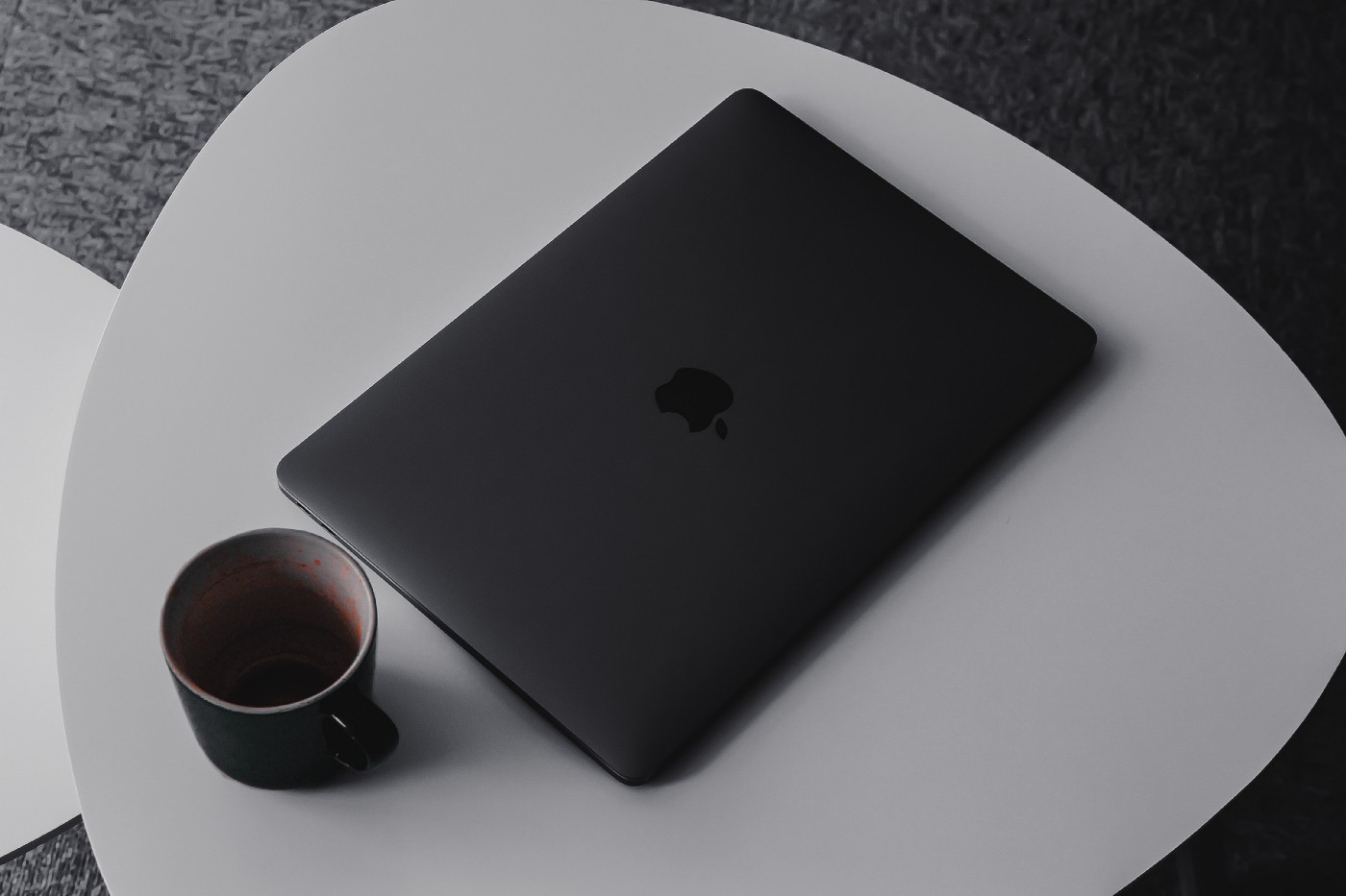A laptop and a cup of coffee lay on a table