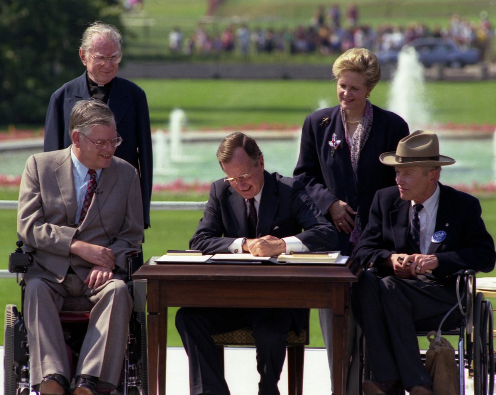 5 people in the image, Bush sitting in the middle and signing the ADA, 2 sitting on a wheelchair, and 2 standing at the back.