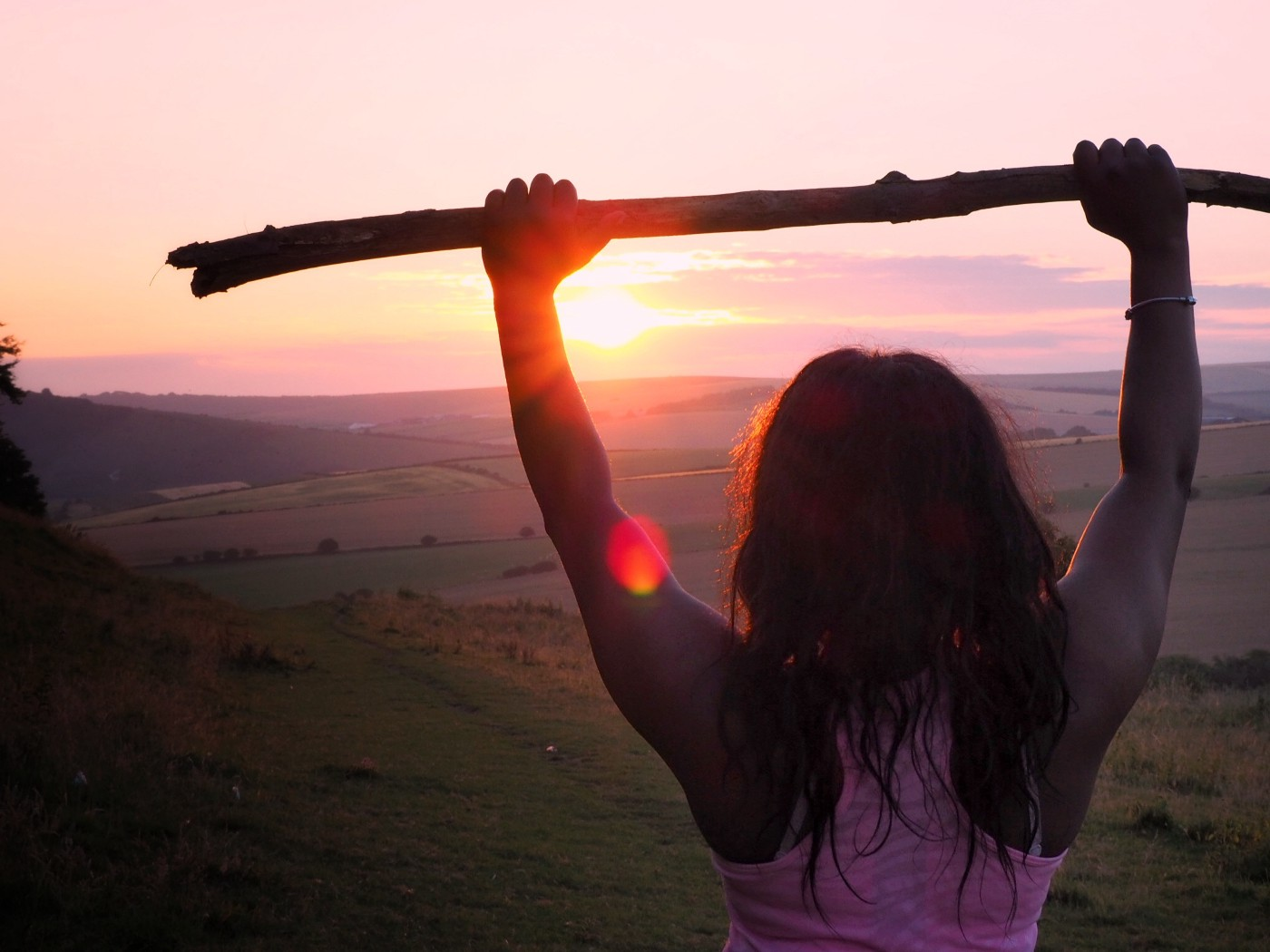 Girl at sunset holding a stick over her head, backlit by the sun.