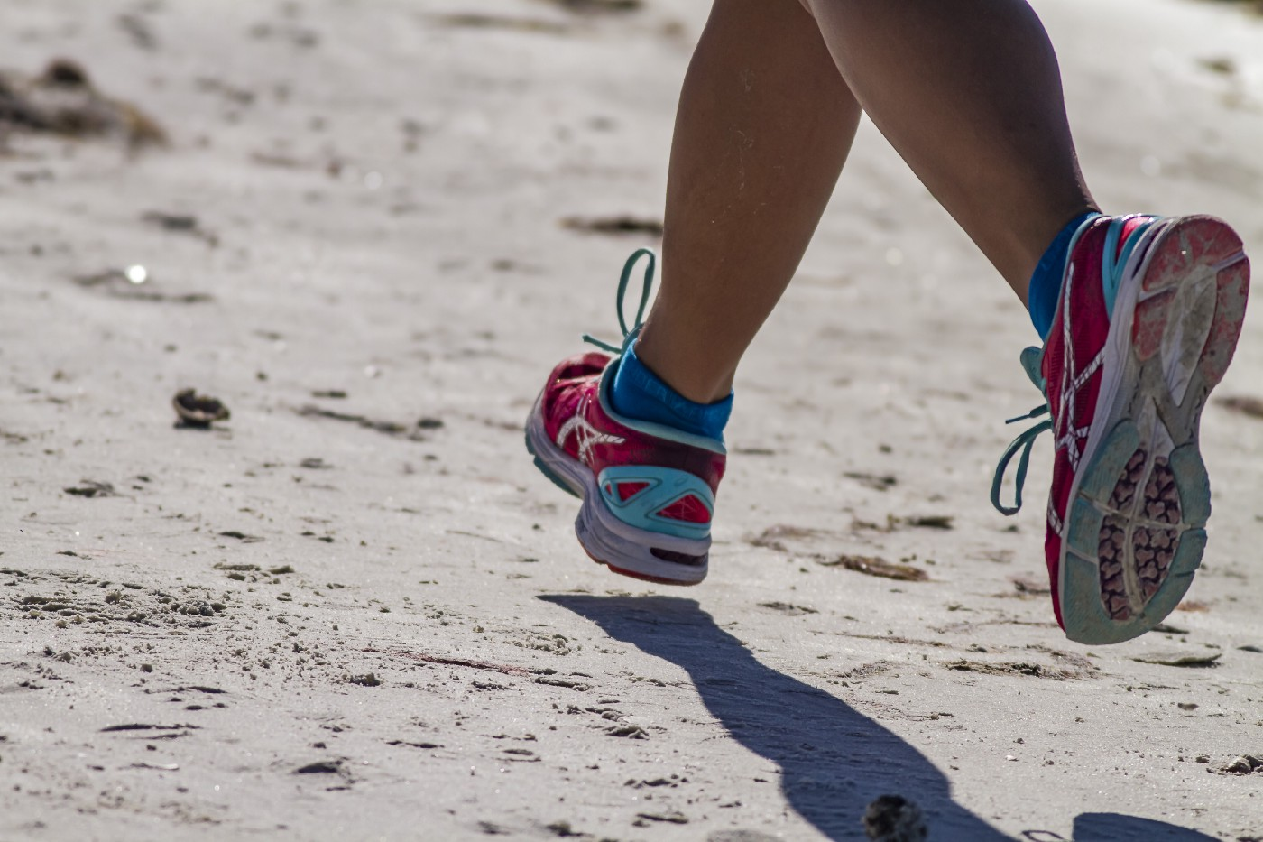 Woman's legs and running shoes on sandy surface