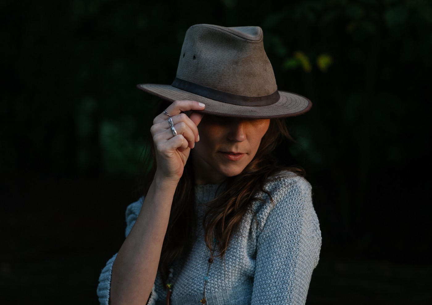 woman looking to the side and touching the brim of her hat
