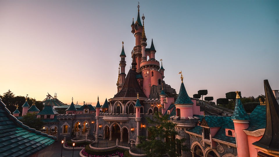 A picture of the castle in Disneyland Paris at sunset.