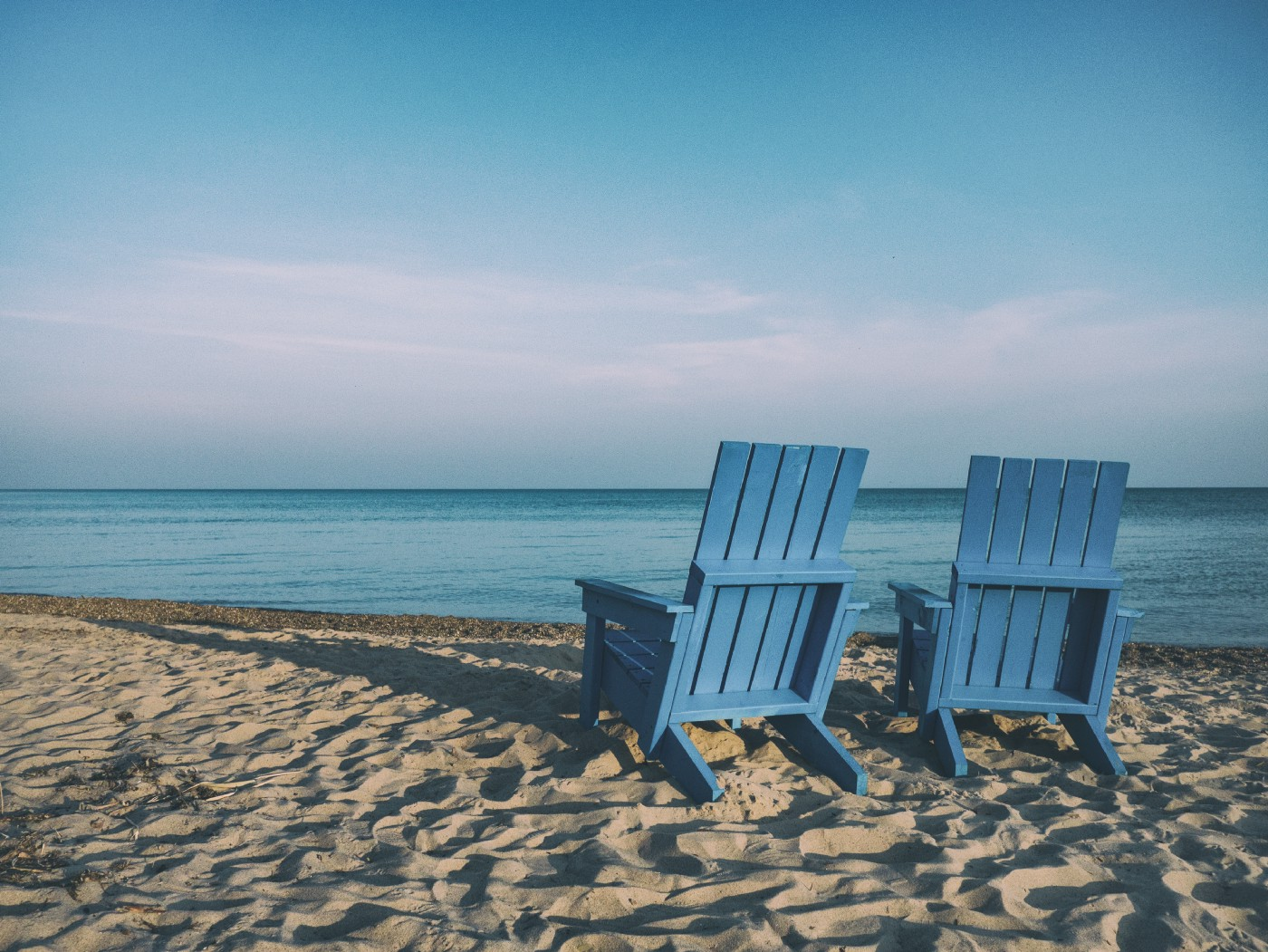 Two blue beach chairs sitting on beach empty. They face the ocean.