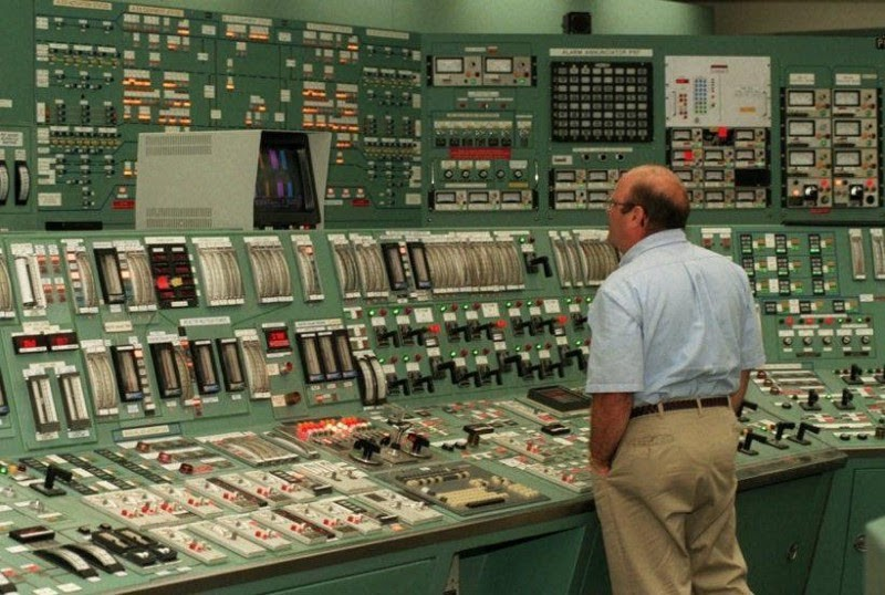 Man staring at a panel of many levers and switches.