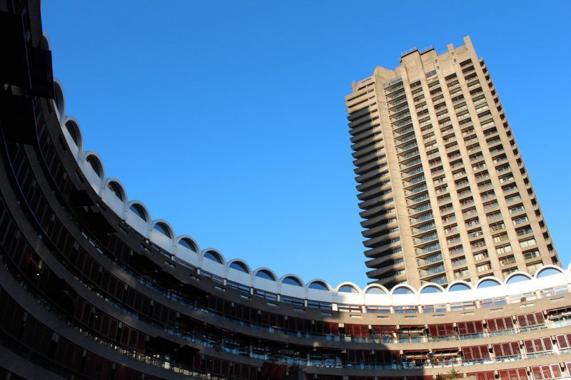 A photograph of a raw concrete tower from London's Barbican Centre taken from ground level on a sunny, cloudless day.
