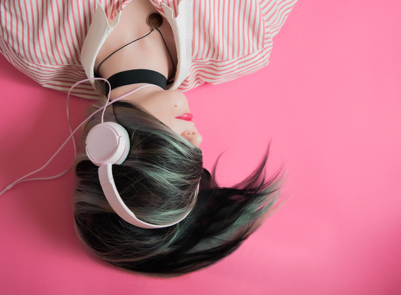 Woman with headphones on and hair hiding hair face lies on her back, head turned sideways
