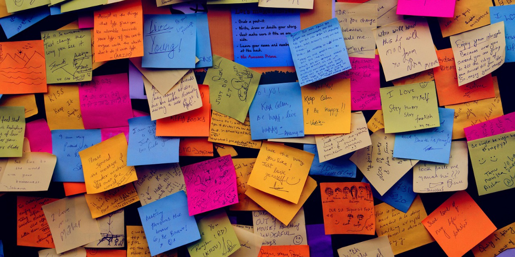 Wall covered in multicolored sticky notes with appreciative messages on them.