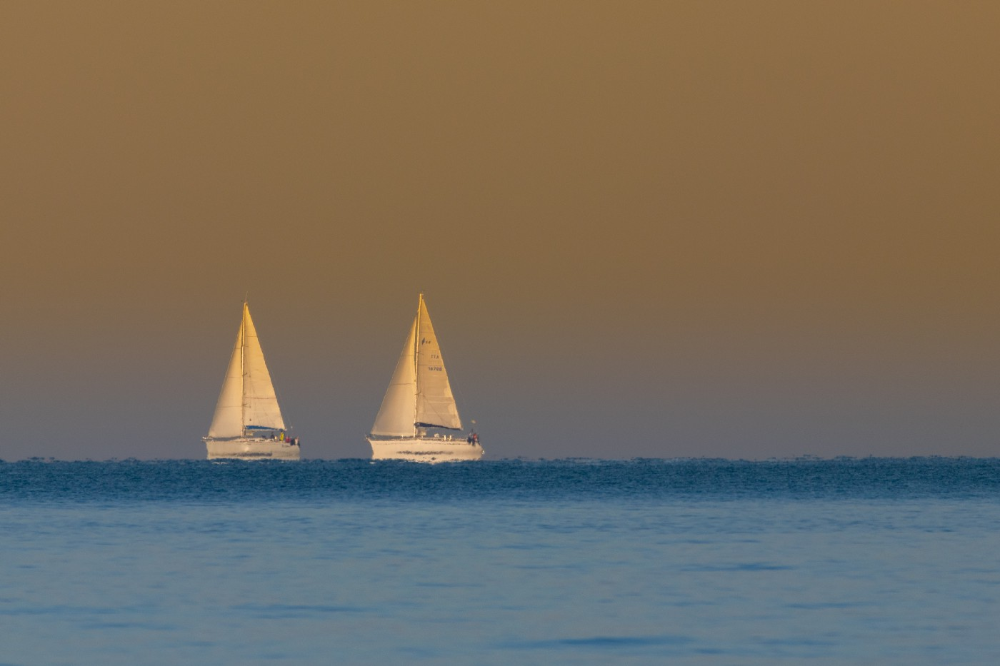 Two sailboats on the horizon of the sea.