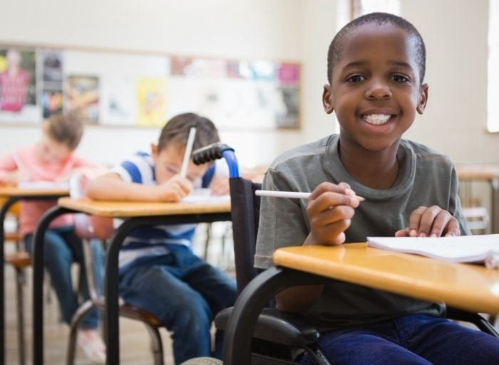 Elementary aged boy in a classroom, smiling, and sitting at a desk while holding a pencil