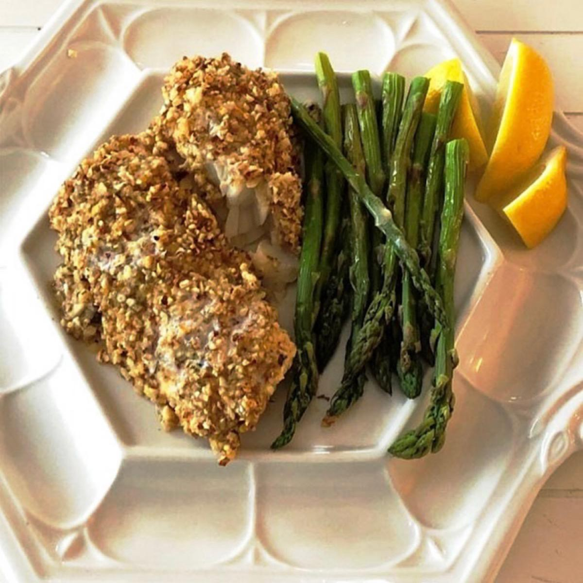 Fish with asparagus on a dinner plate.