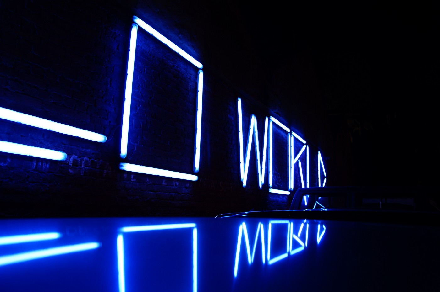 "The word ""WORLD"" spelled in LED lights in a dark room."